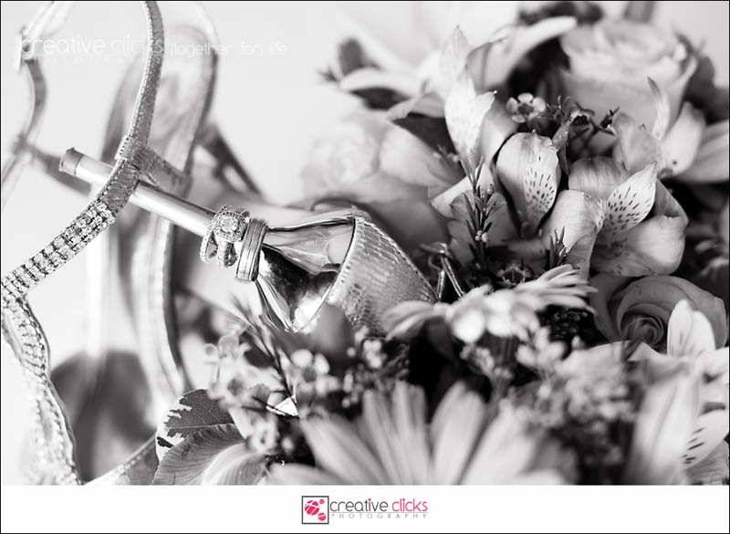 shot of rings on heel of shoes with bouquet